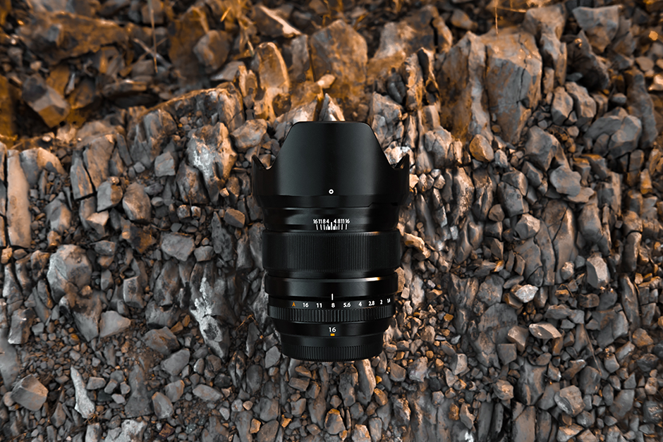 Lens of an SLR Camera amidst a bed of rocks
